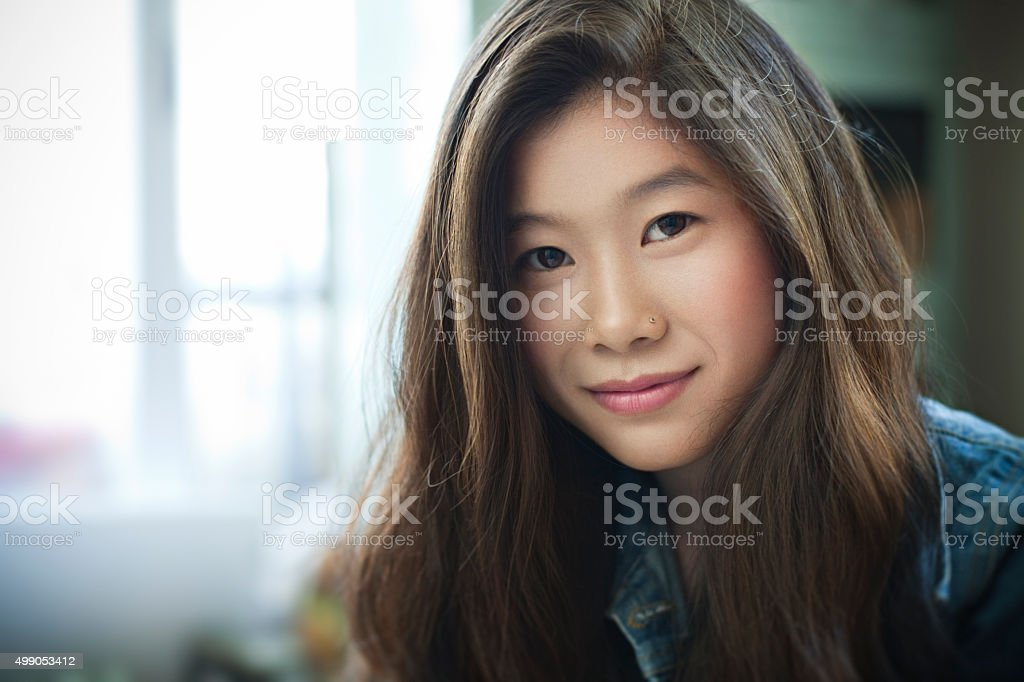Indoor image of beautiful happy Asian girl looking at camera. stock photo