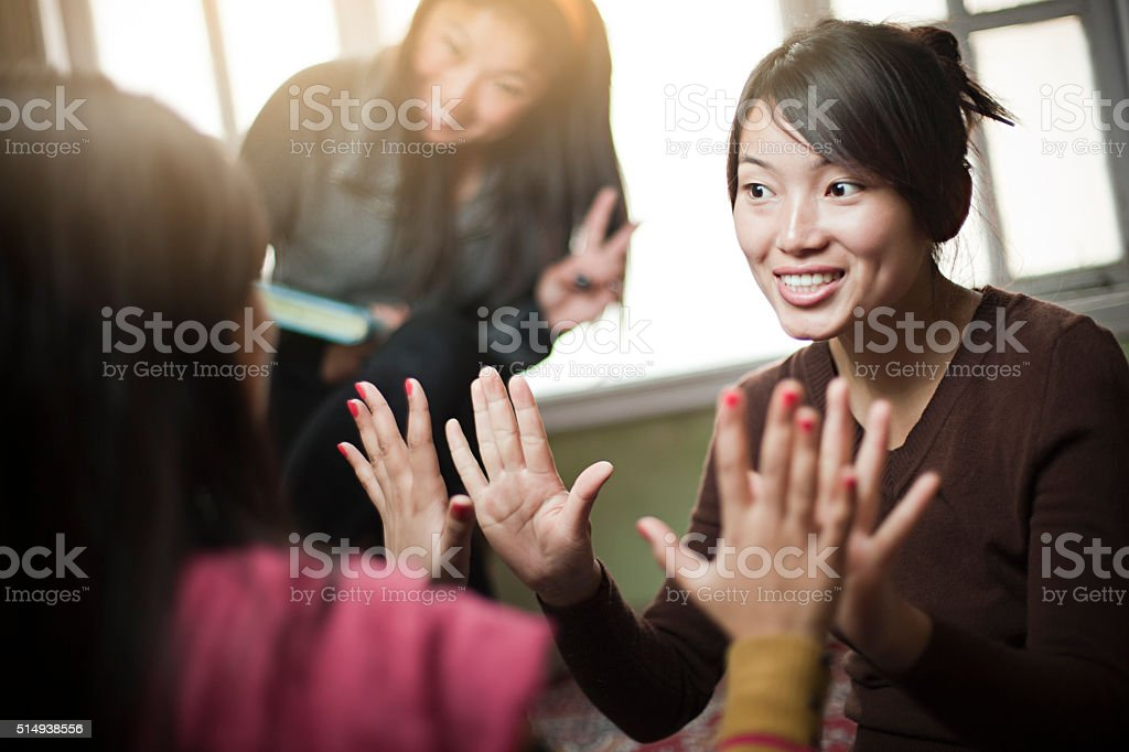 Indoor image of multiracial group of girls playing clapping game. stock photo