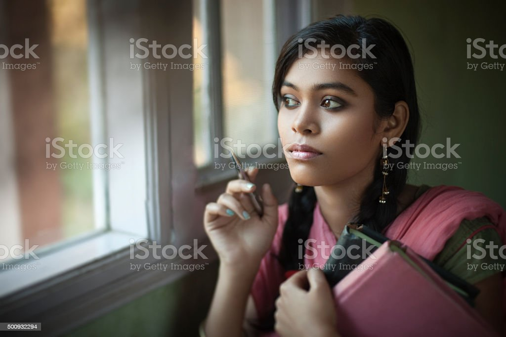Indoor, serene Asian teenage girl student near window with books. stock photo