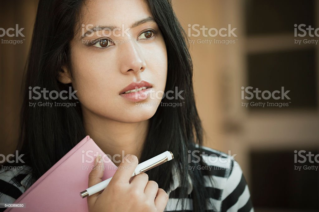 Indoor, serene Asian teenage girl student with book and pen. stock photo