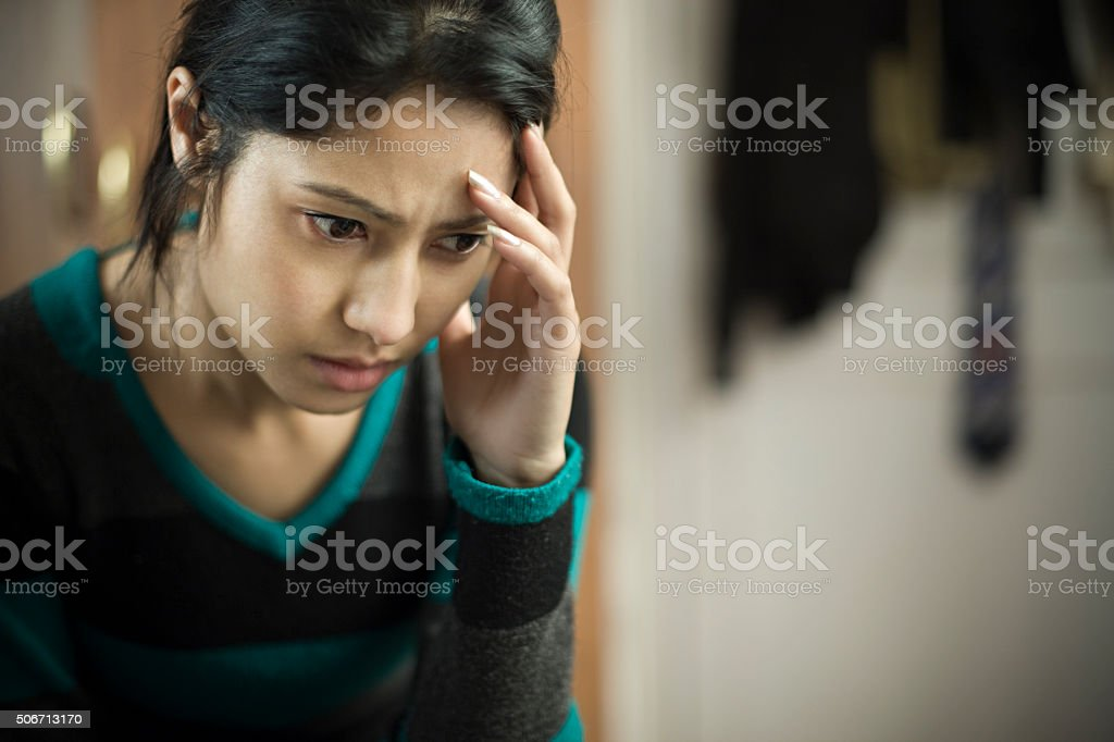 Indoor, serene, stressed young woman touching head and thinking. stock photo