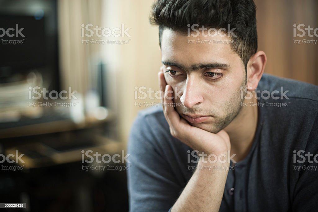 Indoor, serene young man resting head on hand and thinking. stock photo