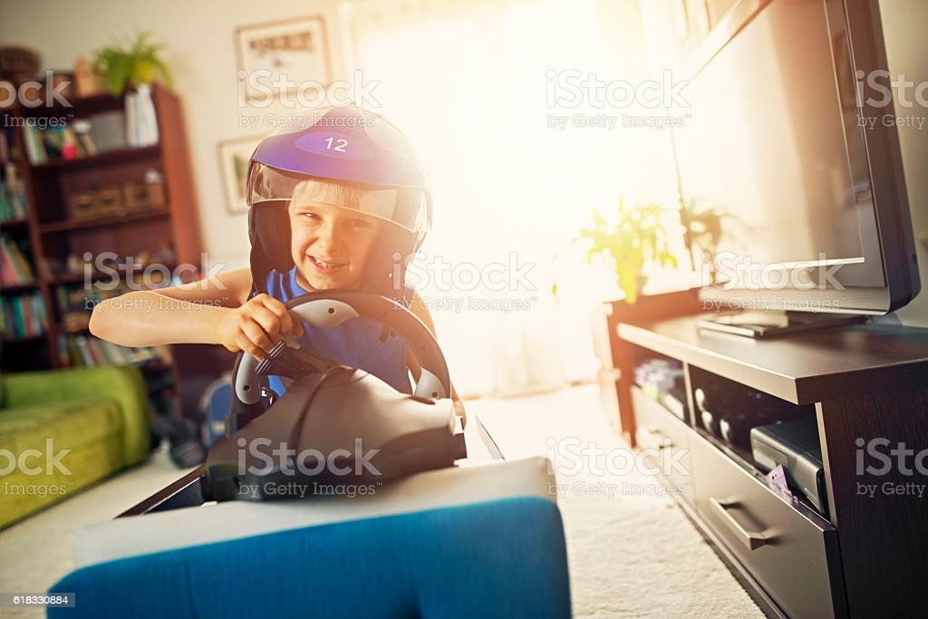 Indoors racing - little boy riding car made from chair stock photo