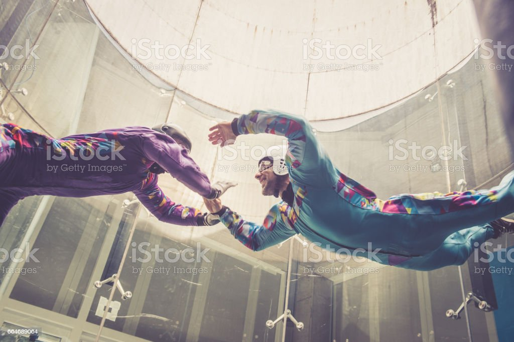 Indoors skydiving -instructor teaching how to fly - freefall simulation stock photo
