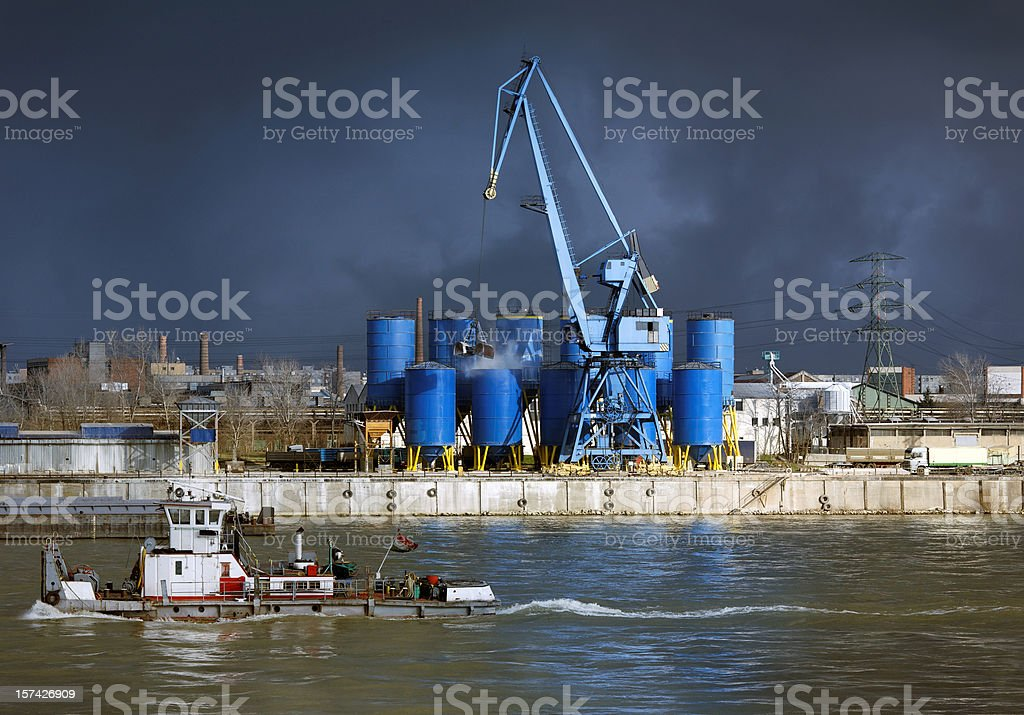 Industrial area with crane and ship before storm stock photo