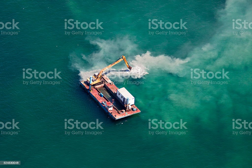 Industrial Barge with an Excavator on the Sea stock photo