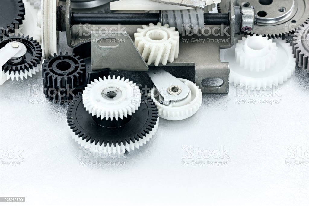 industrial black and white plastic gears on scratched background stock photo