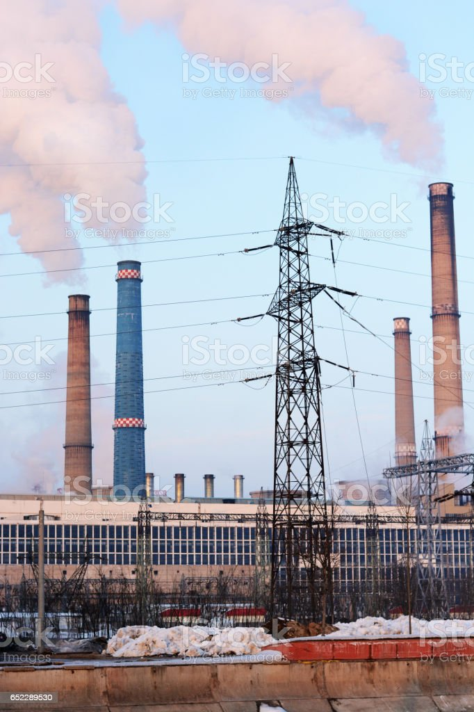 Industrial buildings polluting air with co-generation plant blowing smoke out of its chimneys stock photo