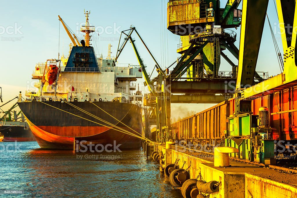 Industrial cargo ship with working crane in port stock photo