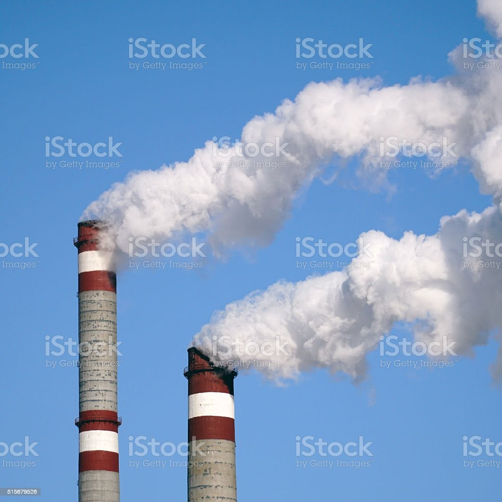 industrial chimneys emits toxic pollutants into the sky polluting environment stock photo