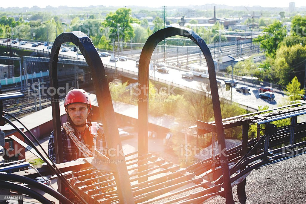 Industrial climber climbs to the roof of the building stock photo