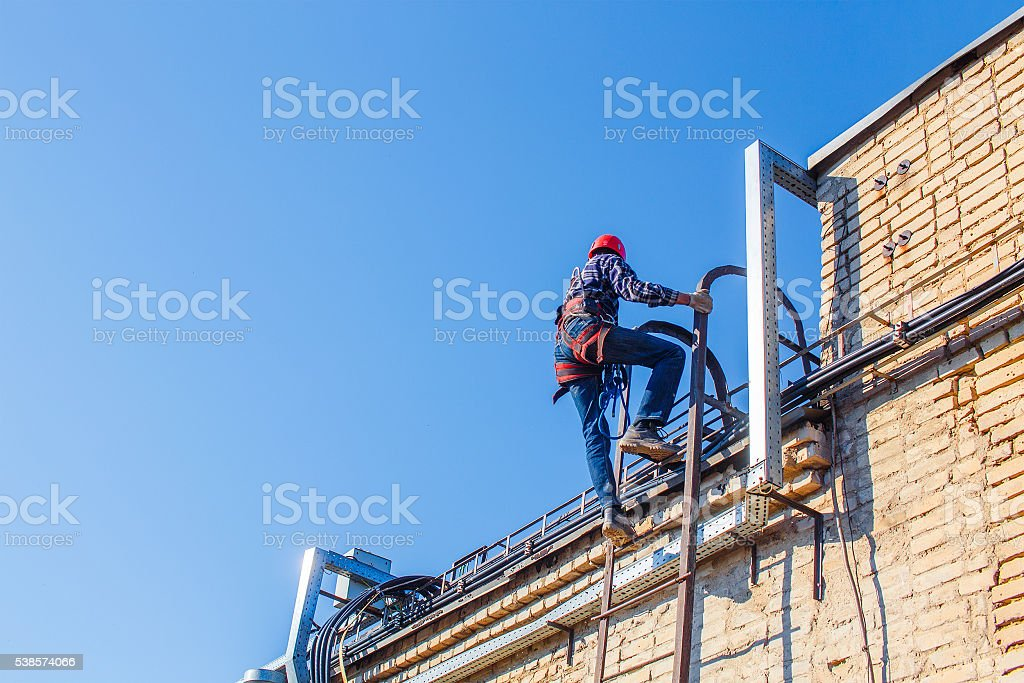 Industrial climber climbs up the stairs to the roof stock photo
