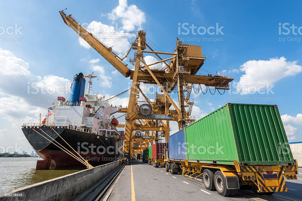Industrial Container Cargo freight ship with working crane stock photo