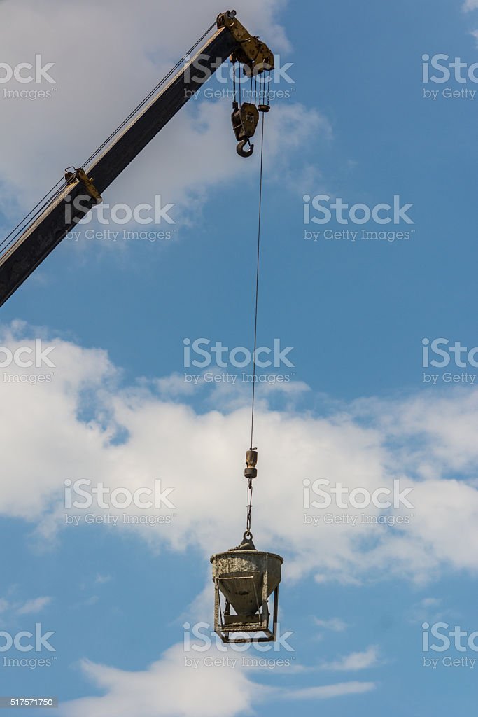 Industrial crane lifting cement mixing container to construction stock photo