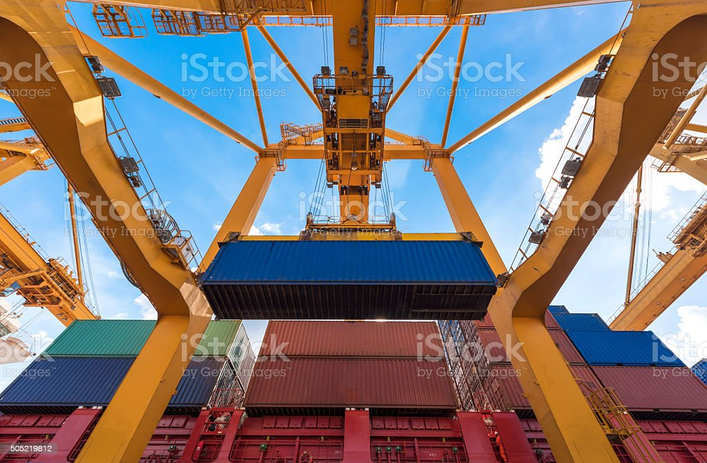 Industrial crane loading Containers in a Cargo freight ship stock photo
