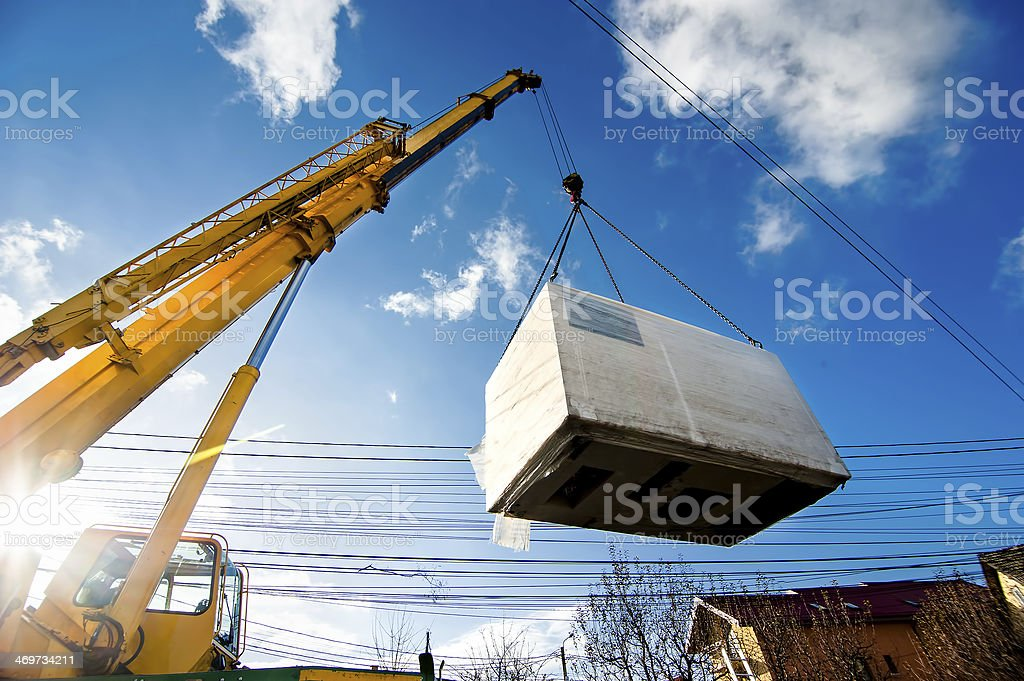 Industrial Crane operating and lifting an electric generator stock photo