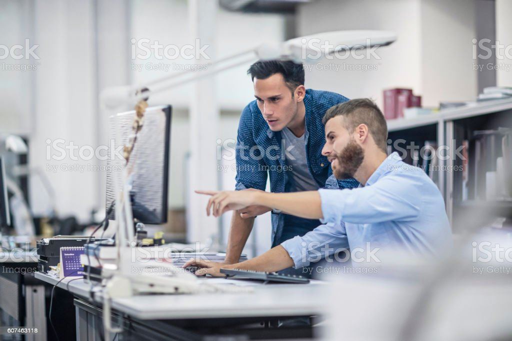 Industrial designers at the office discussing project on the computer royalty-free stock photo