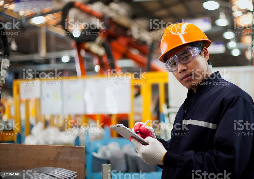 Industrial engineer looking away while writing on a pad stock photo