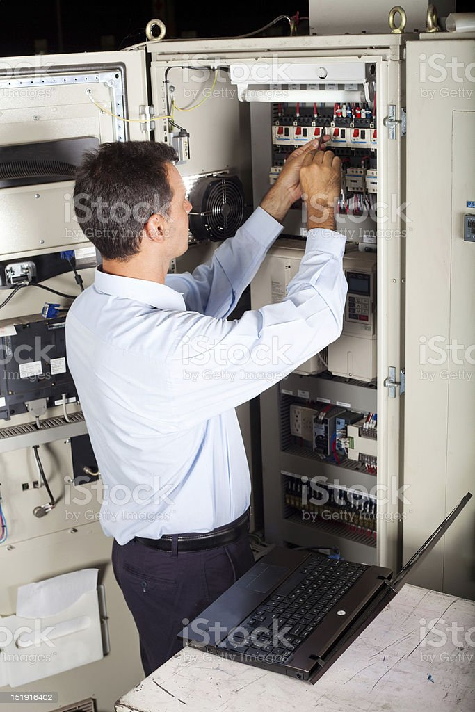 industrial engineer repairing computerized machine royalty-free stock photo