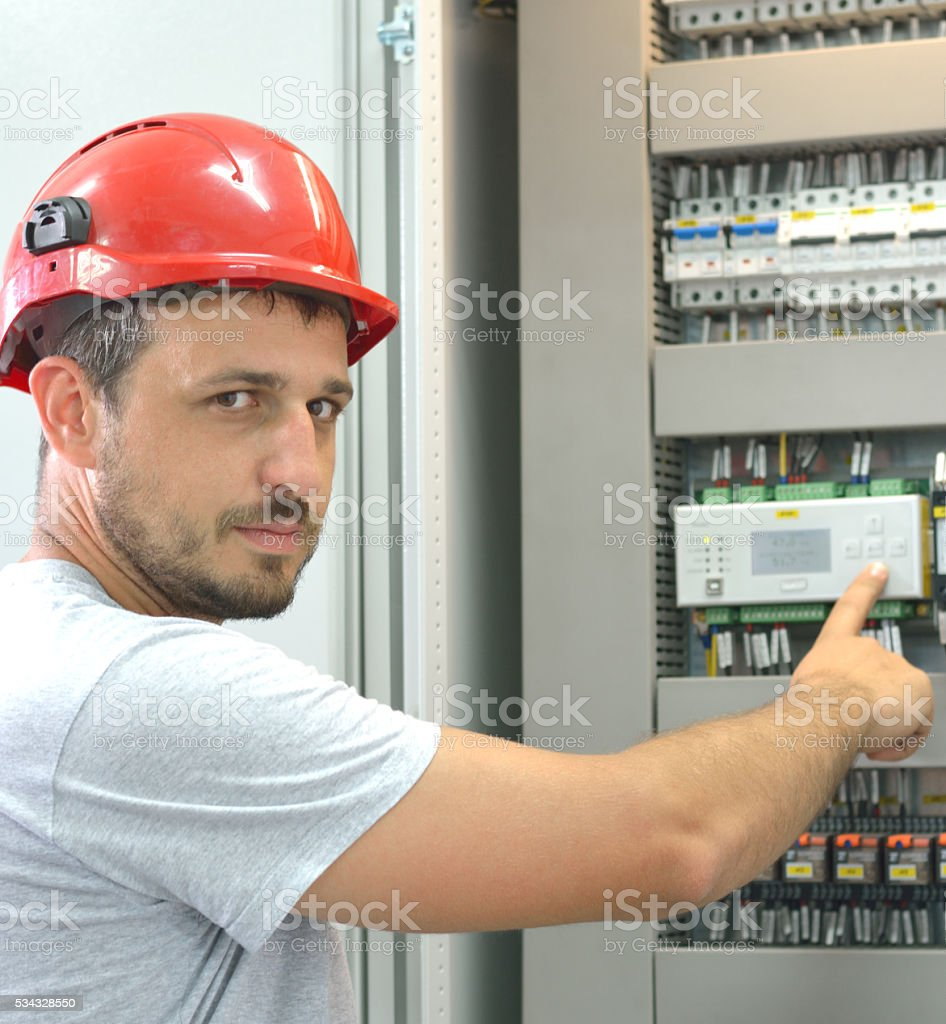 Industrial Engineer Touching Control Panel and Looking at Camera stock photo