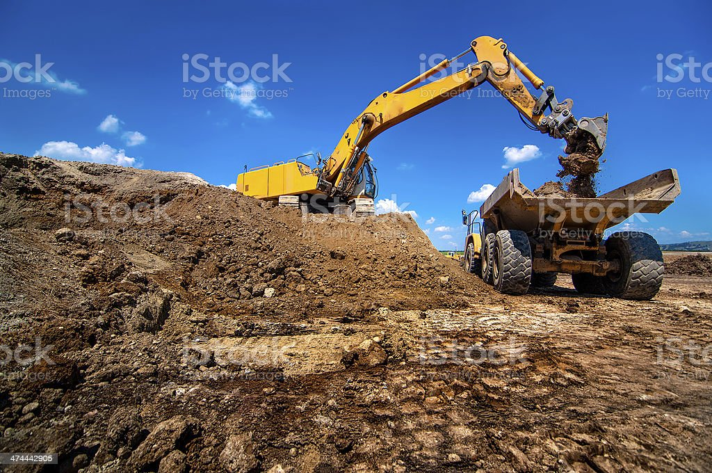 Industrial excavator loading soil material from highway construc stock photo