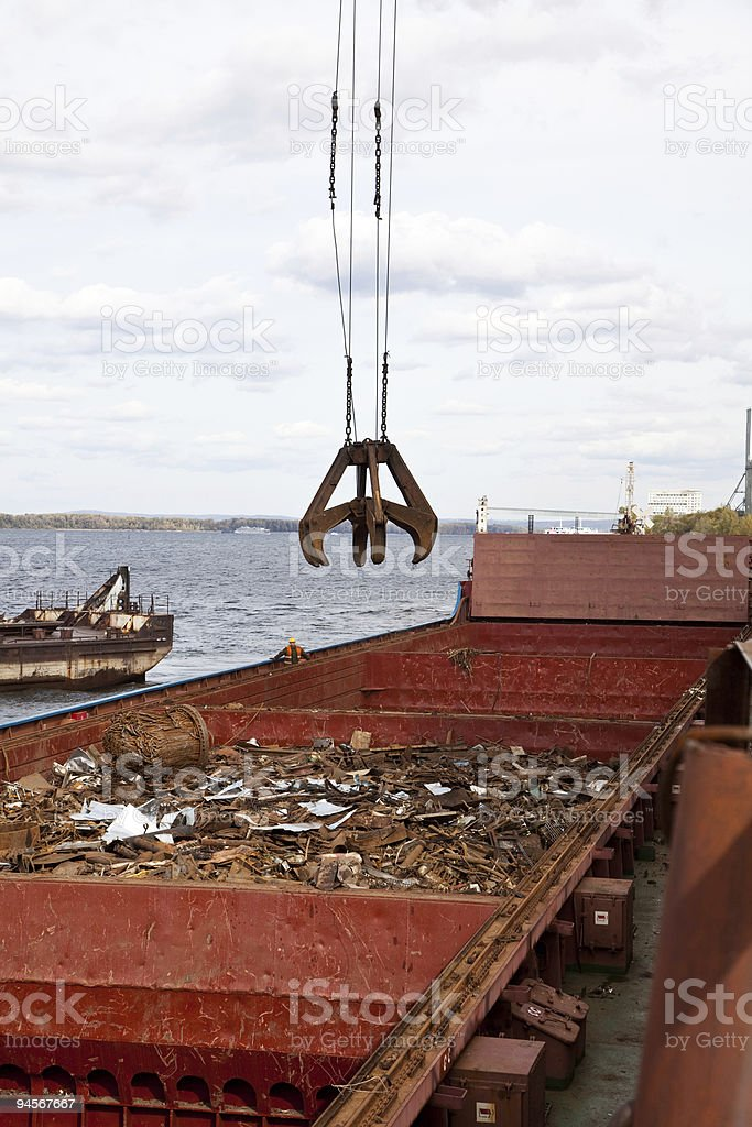 Industrial grabber loads the barge scrap metal royalty-free stock photo