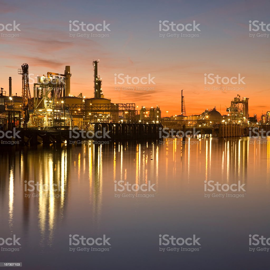 Industrial harbor lit up at sunset royalty-free stock photo