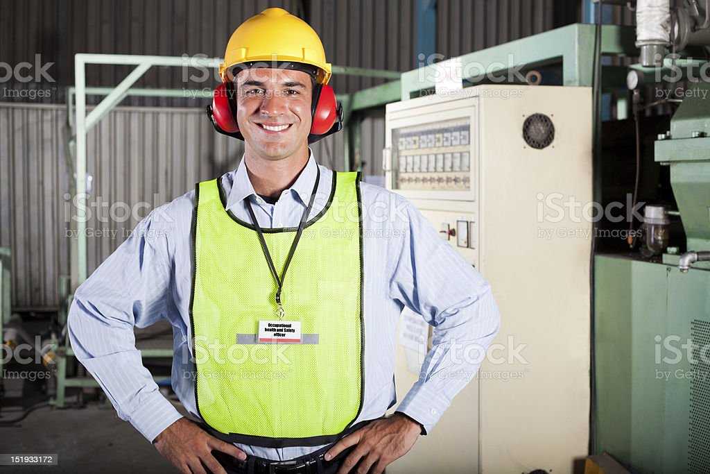 happy male industrial health and safety officer portrait inside...