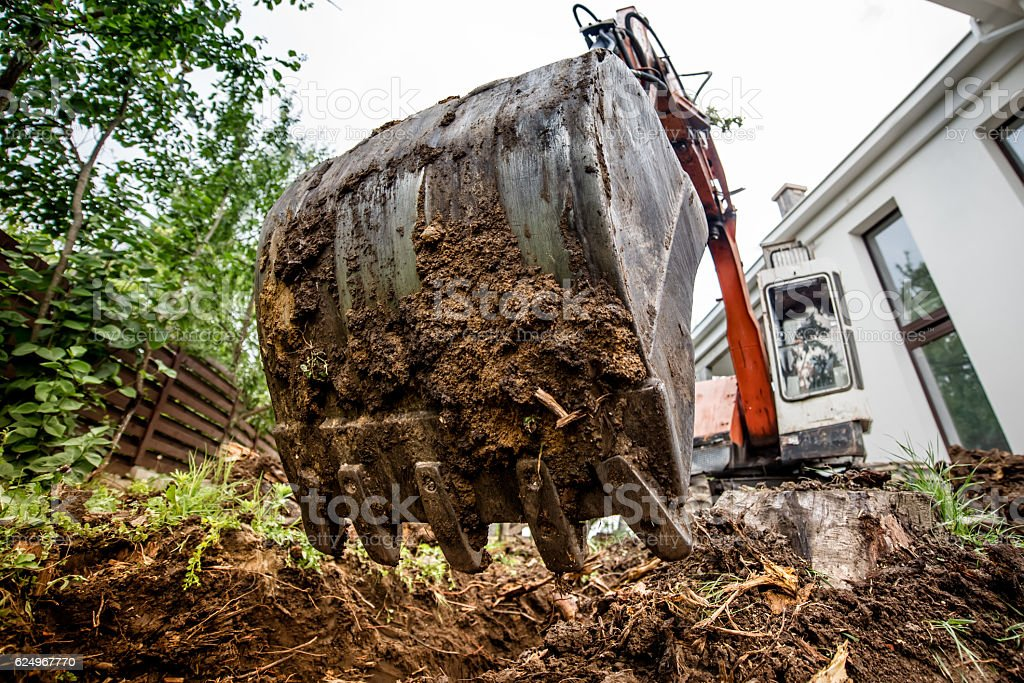industrial heavy duty excavator digging at construction site stock photo