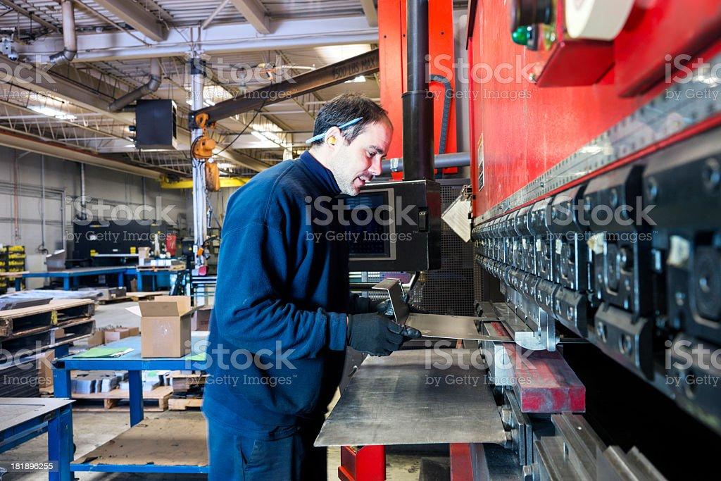 Industrial machine operator working a brake press stock photo