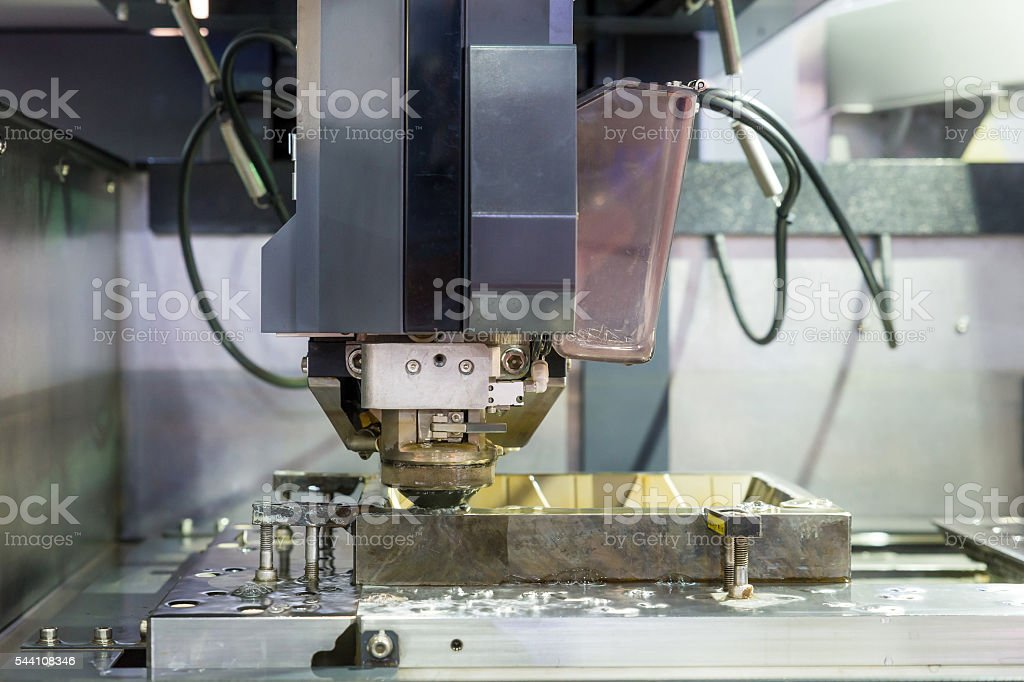 EDM Industrial machine working with coolant injection in factory. stock photo