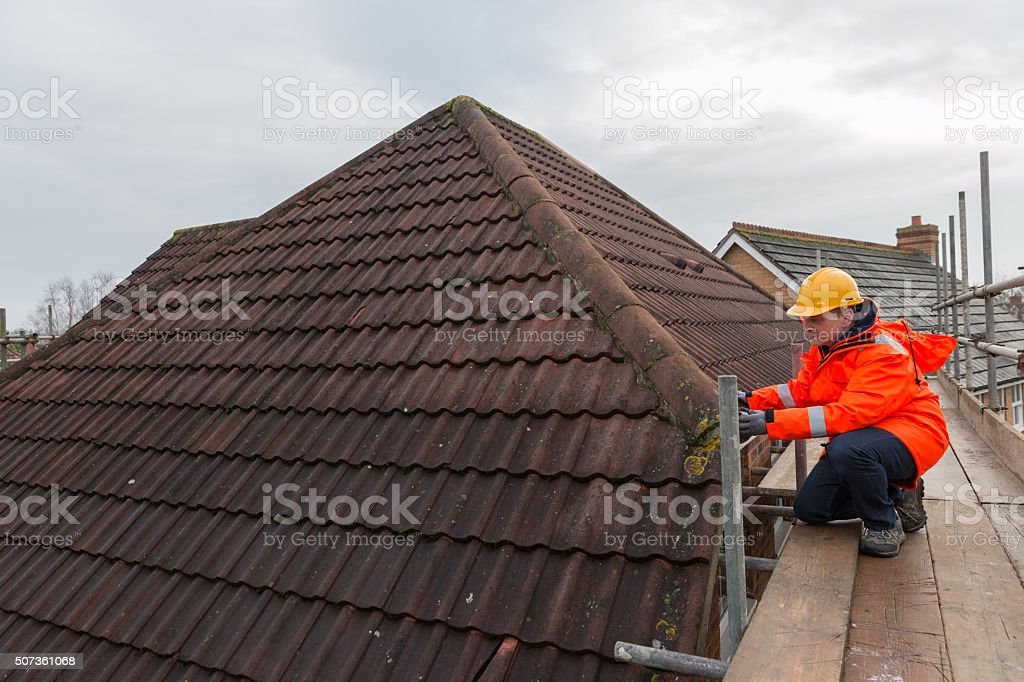 Industrial male builder working on building site roof tile repair stock photo