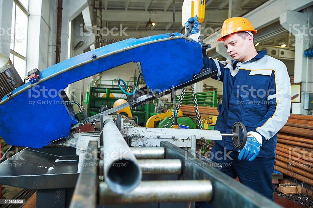 industrial male worker operating bandsaw in manufacturing factory stock photo