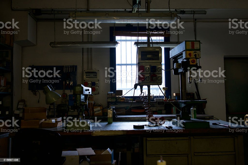 Industrial mechanics work bench and drilling tools in backlight stock photo
