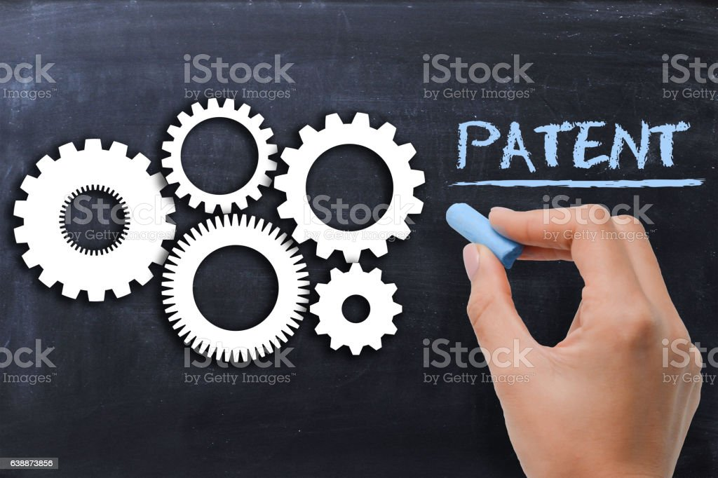 Industrial patent protection concept with gears on blackboard stock photo