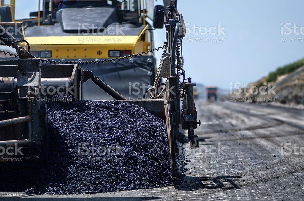 Industrial pavement machine laying fresh asphalt on highway stock photo