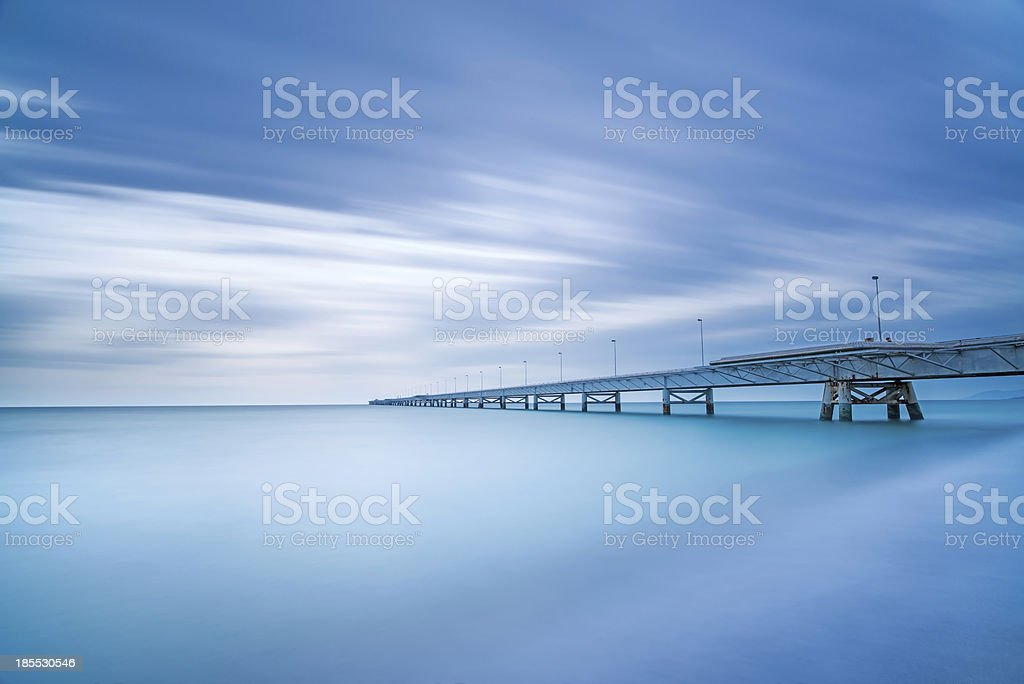 Industrial pier on the sea. Side view. Long exposure photography. royalty-free stock photo