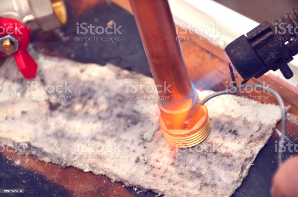 Industrial plumber using blowtorch, propane gas torch for welding pipes stock photo