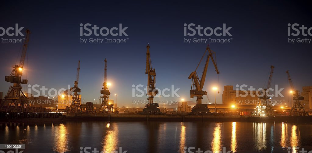 A industrial port by the water at night stock photo