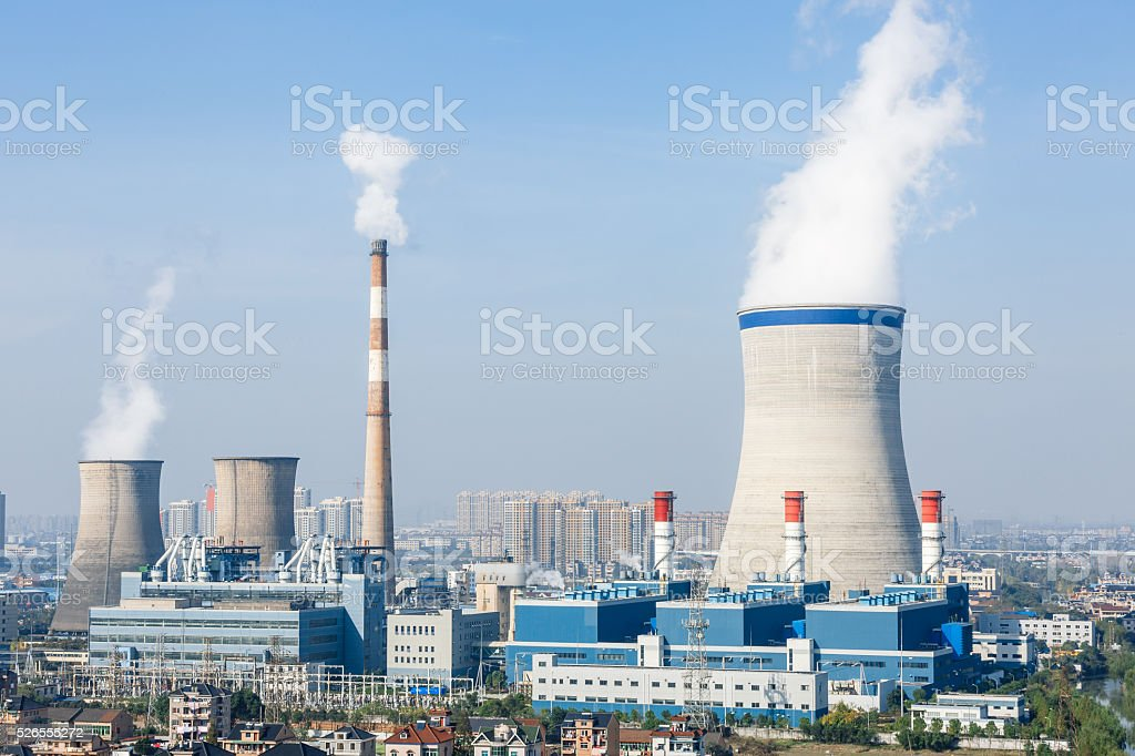 Industrial power plant smoke pollution in the blue sky stock photo