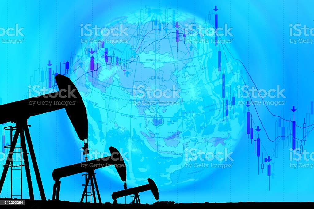 industrial pump jack and falling oil graph on globe background stock photo