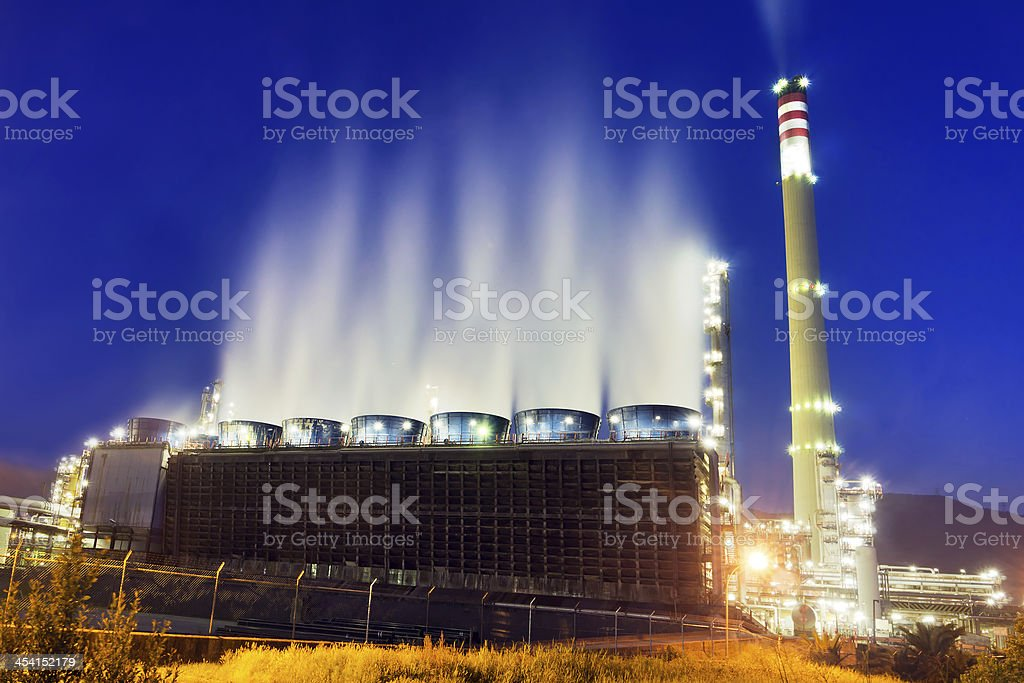 industrial refinery at night with cooling water smoke stock photo