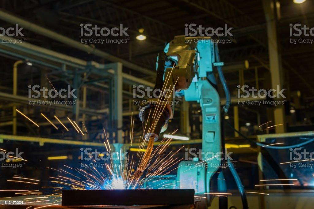 Industrial robot is welding automotive part in automotive industrial...