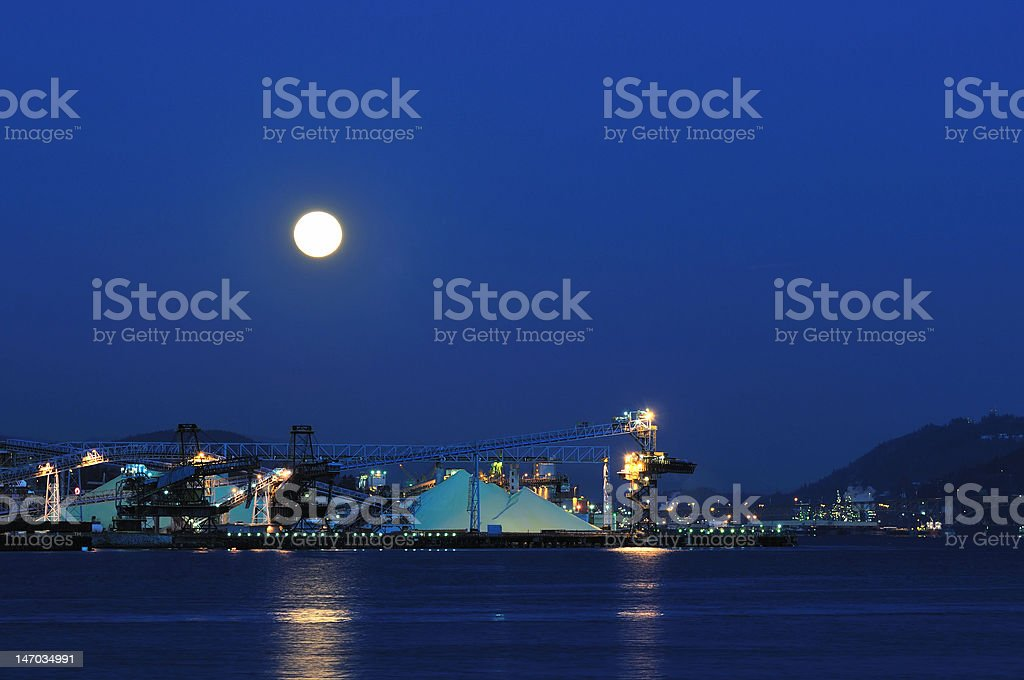 Industrial shipping dock at Burrard inlet under moonlight royalty-free stock photo