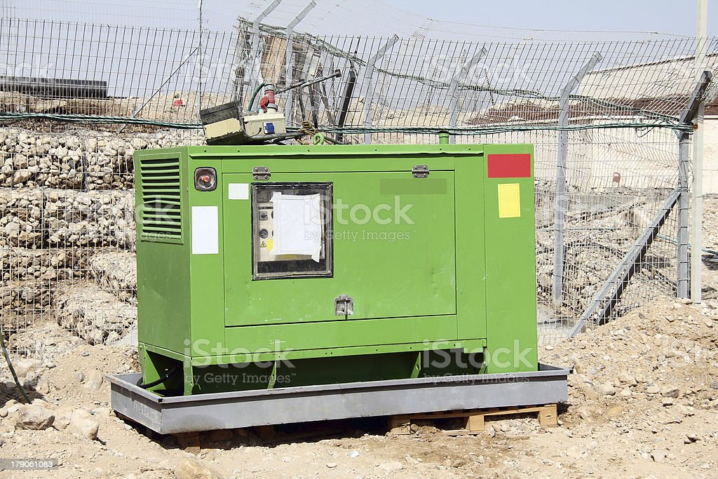 Industrial sized green electrical power generator outdoors stock photo