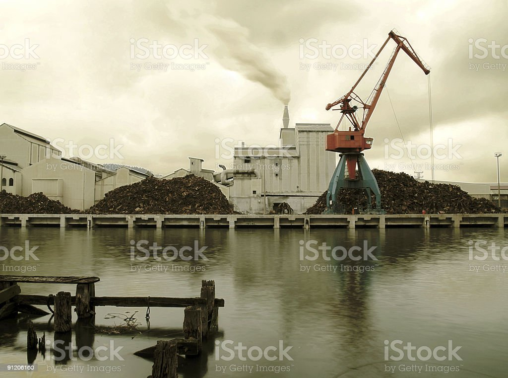 Industrial smoking chimney and crane by the river stock photo