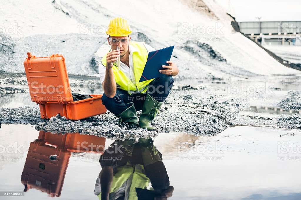 industrial worker checking quality of iron ore stock photo
