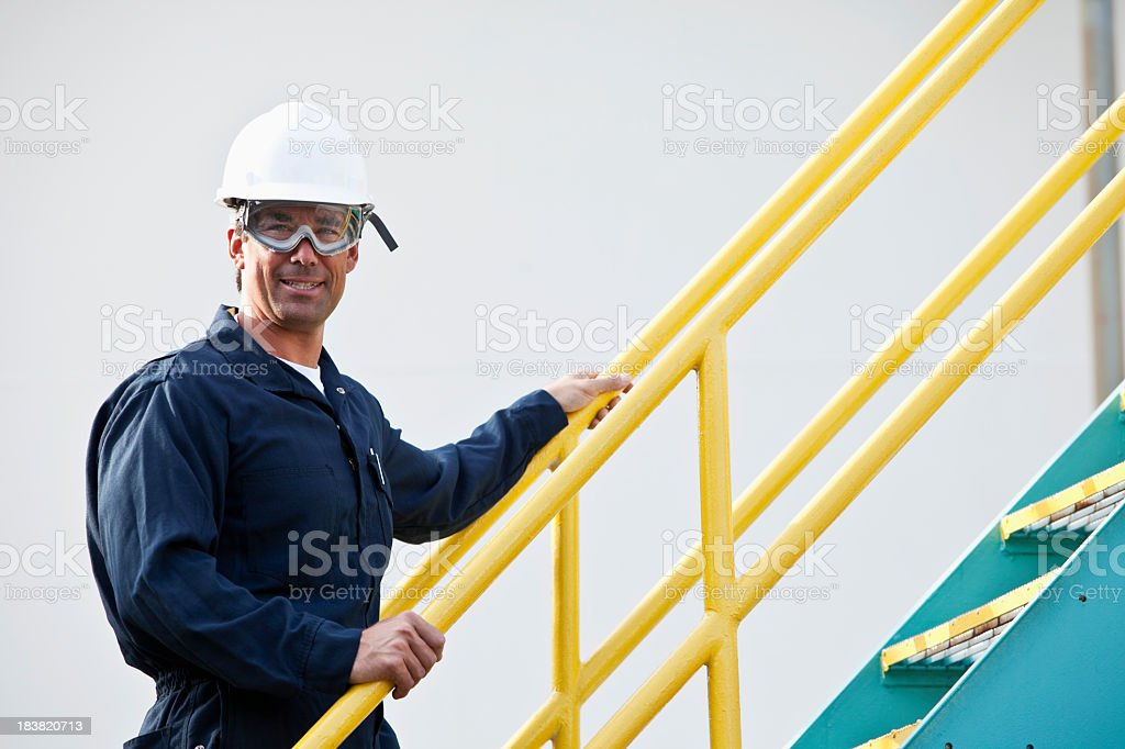 Industrial worker climbing metal staircase royalty-free stock photo