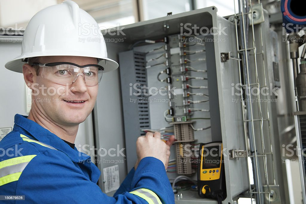 Industrial worker in a hard hat working on a circuit box royalty-free stock photo