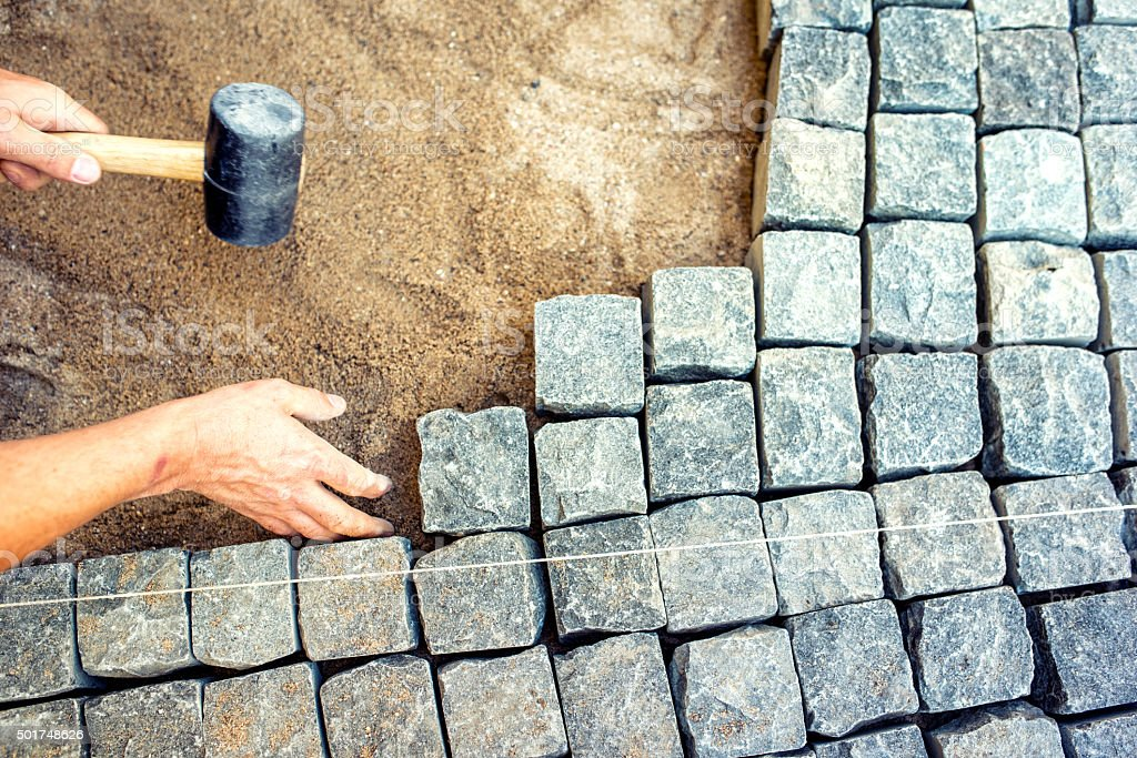 industrial worker installing pavement rocks, cobblestone blocks on road pavement stock photo